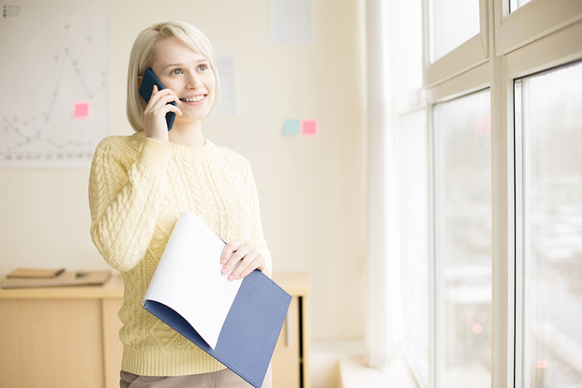 woman on phone looking out of office window