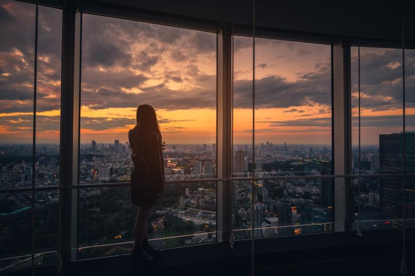 woman looking at city skyline at night