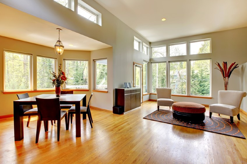 Large dining room and living room in a modern house with many windows.